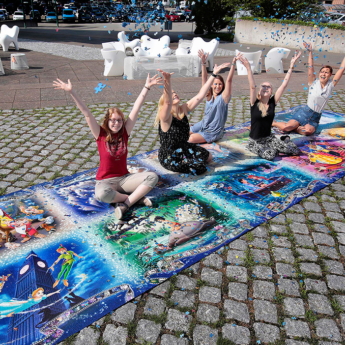 Ravensburger employees sitting on the biggest puzzle in the world